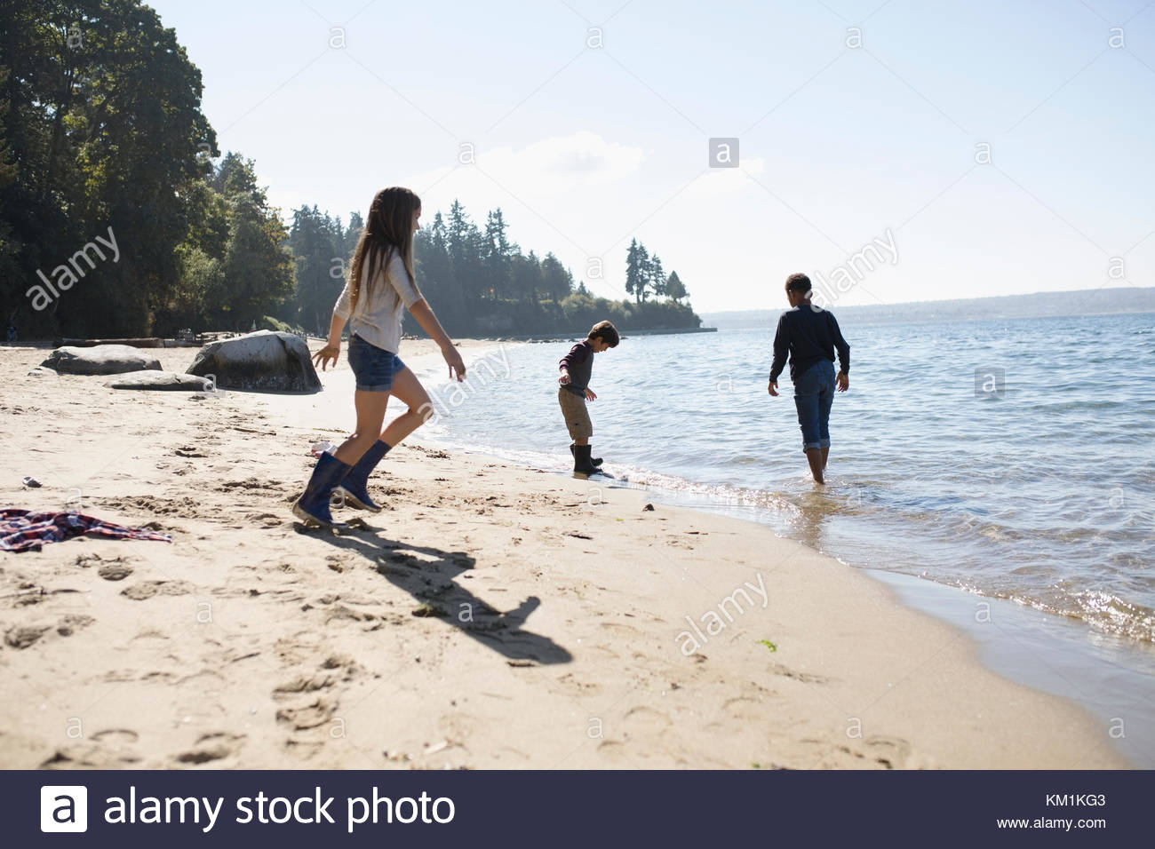 Boy and girl friends playing on sunny ocean beach - Stock Image