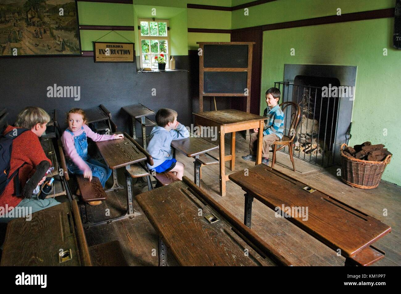 Bunratty Folk Park, Bunratty Castle, Co. Clare, Ireland. Children pupils and mother teacher explore the School House - Stock Image