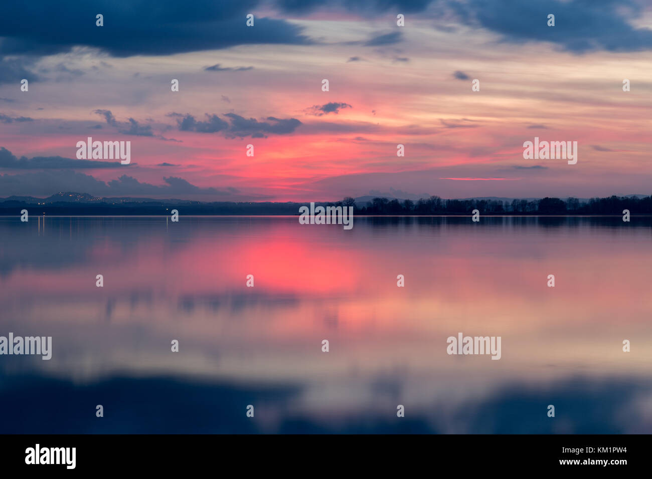 Perfectly symmetric reflection of  sunset on a  lake, with warm tones in the sky and water - Stock Image