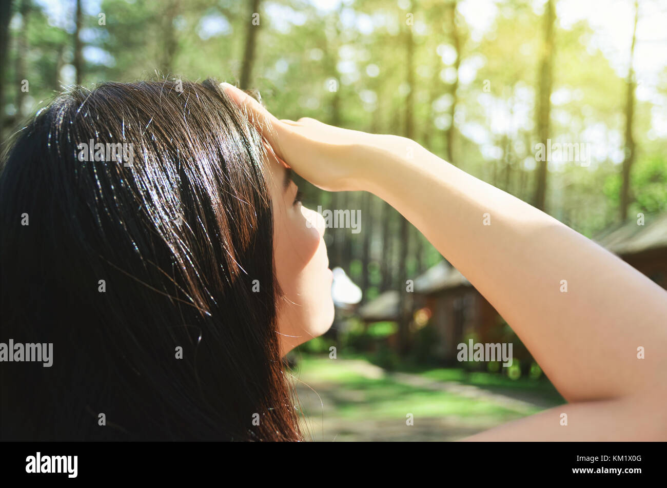 Asian girl covering her eyes from bright sunshine - Stock Image