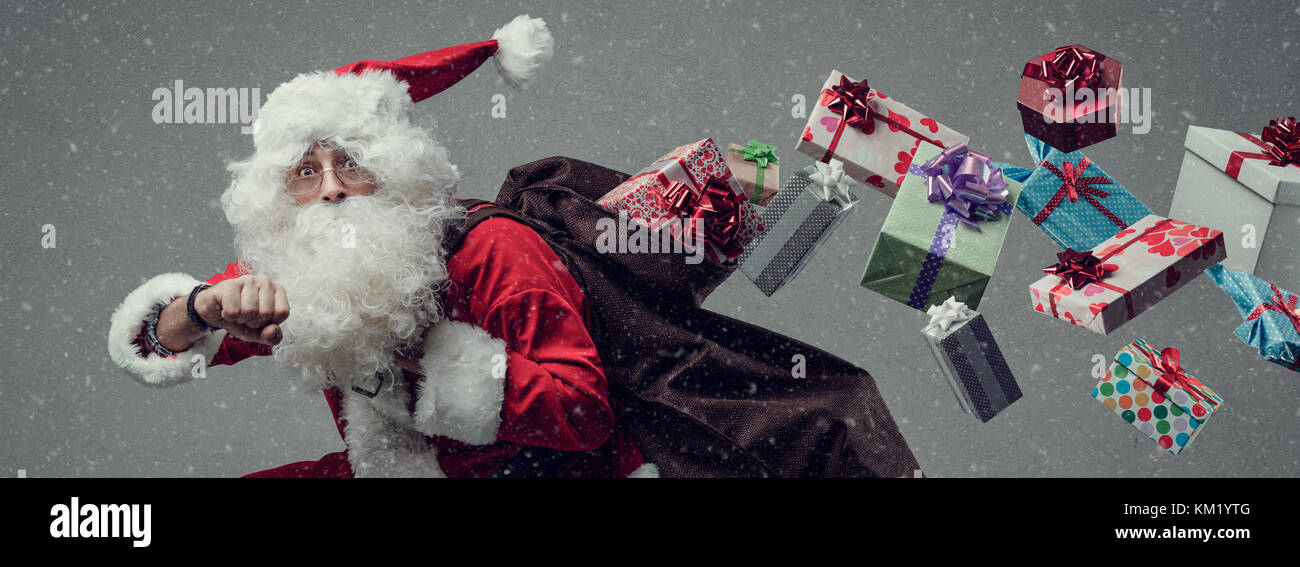 Santa Claus running and delivering Christmas presents: he is late and losing gifts from his sack - Stock Image