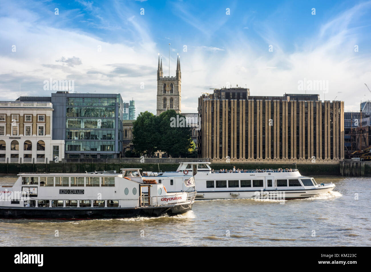 Two tour cruise boats on the river Thames and a view of the southbank - Stock Image