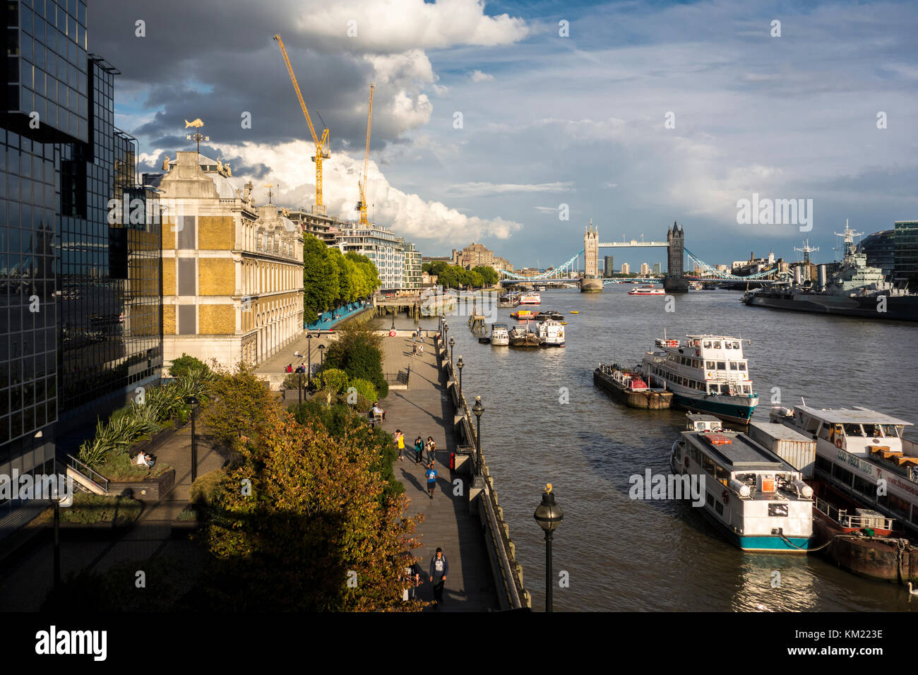 View along the Thames towards Tower Bridge looking down on Old Billingsgate Walk and Dark House Walk, Thames path. Stock Photo