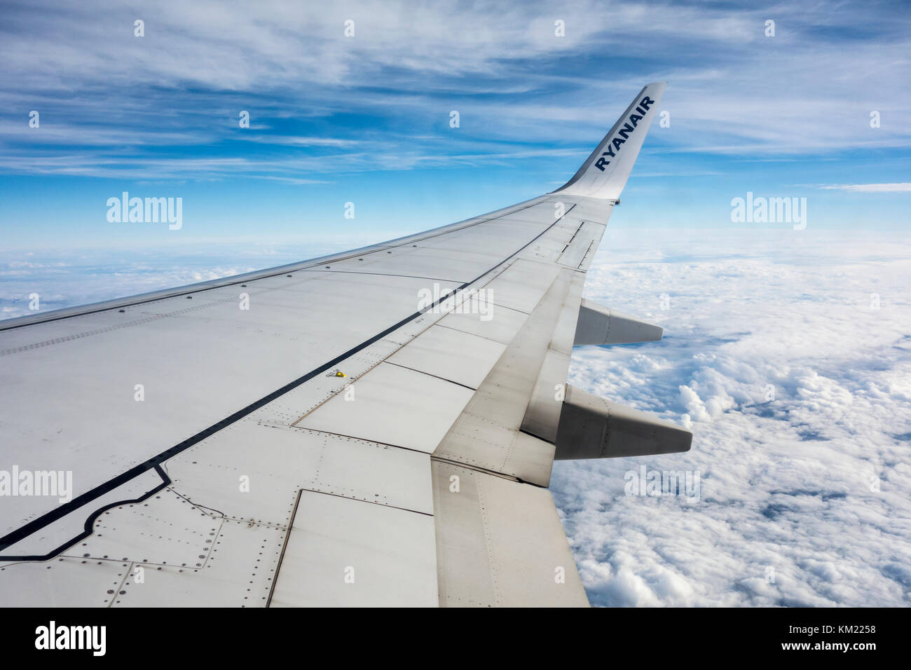 View from a plane window of a wing and Ryanair logo - Stock Image