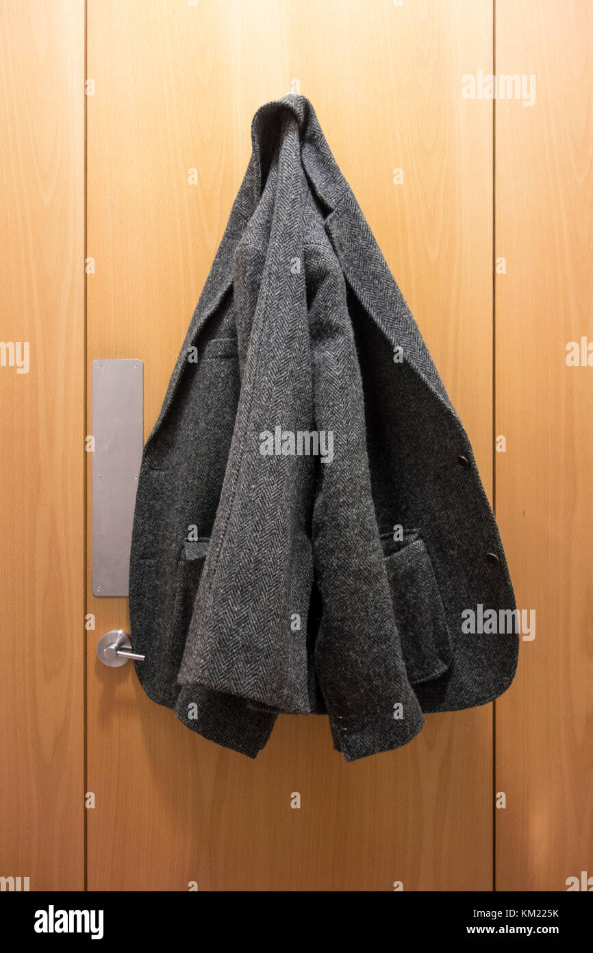 Tweed jacket hung up on the inside of a toilet cubicle door - Stock Image
