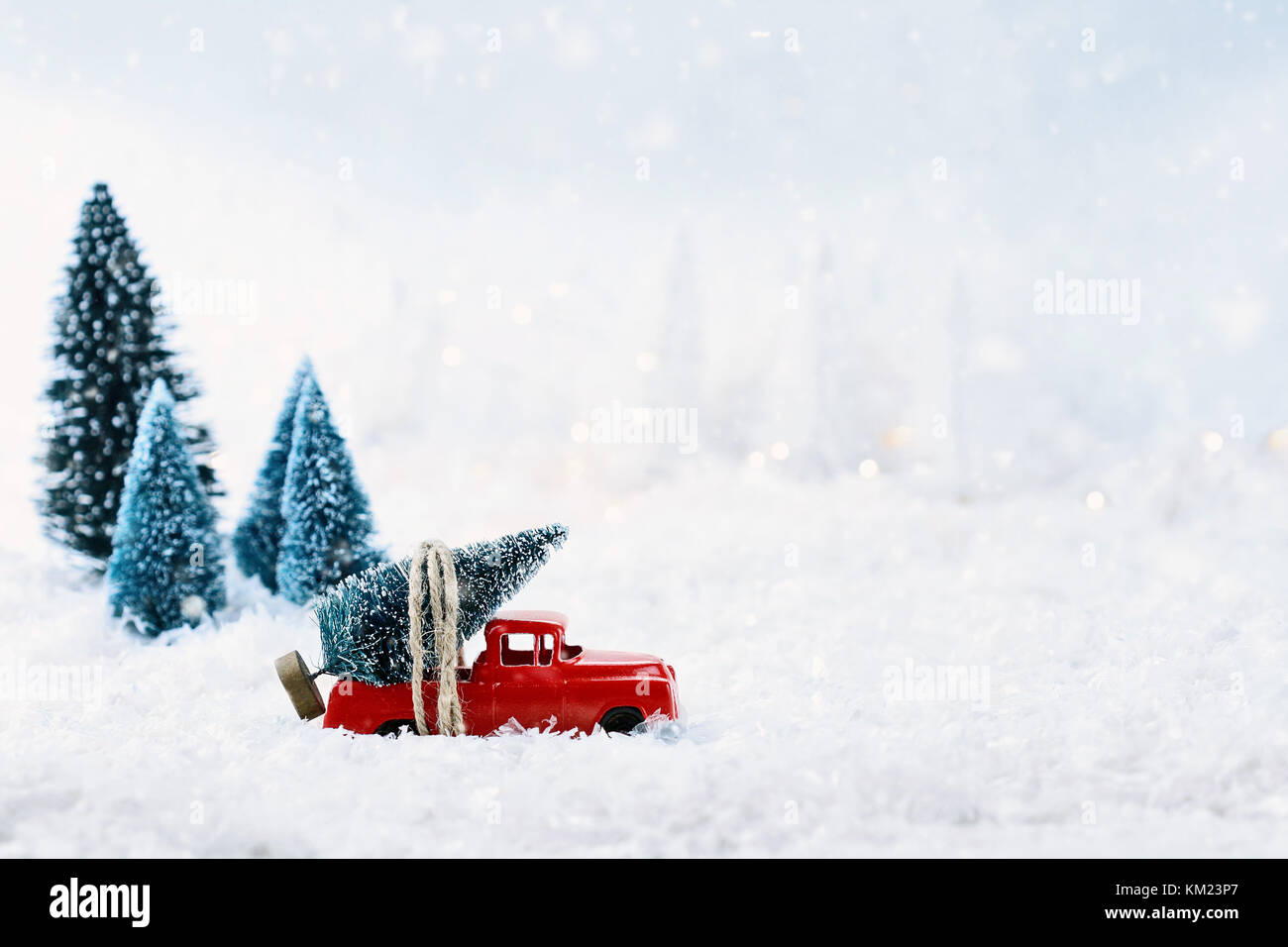 1950s antique vintage red truck hauling a christmas tree home through a snowy winter wonder land