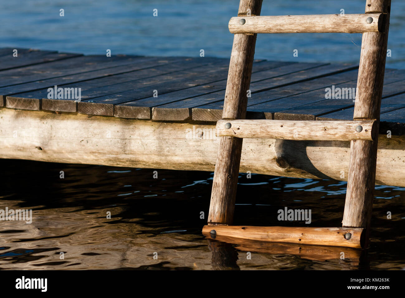 Wooden ladder and a lakeside dock in cottage country - Stock Image