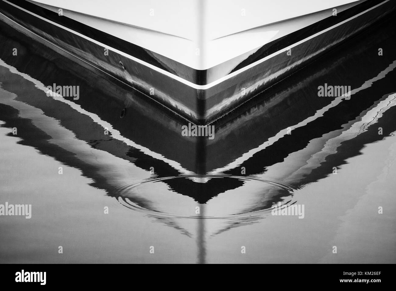 Ripples from a water drop mar the reflection of a yacht's bow on the surface of the water. - Stock Image