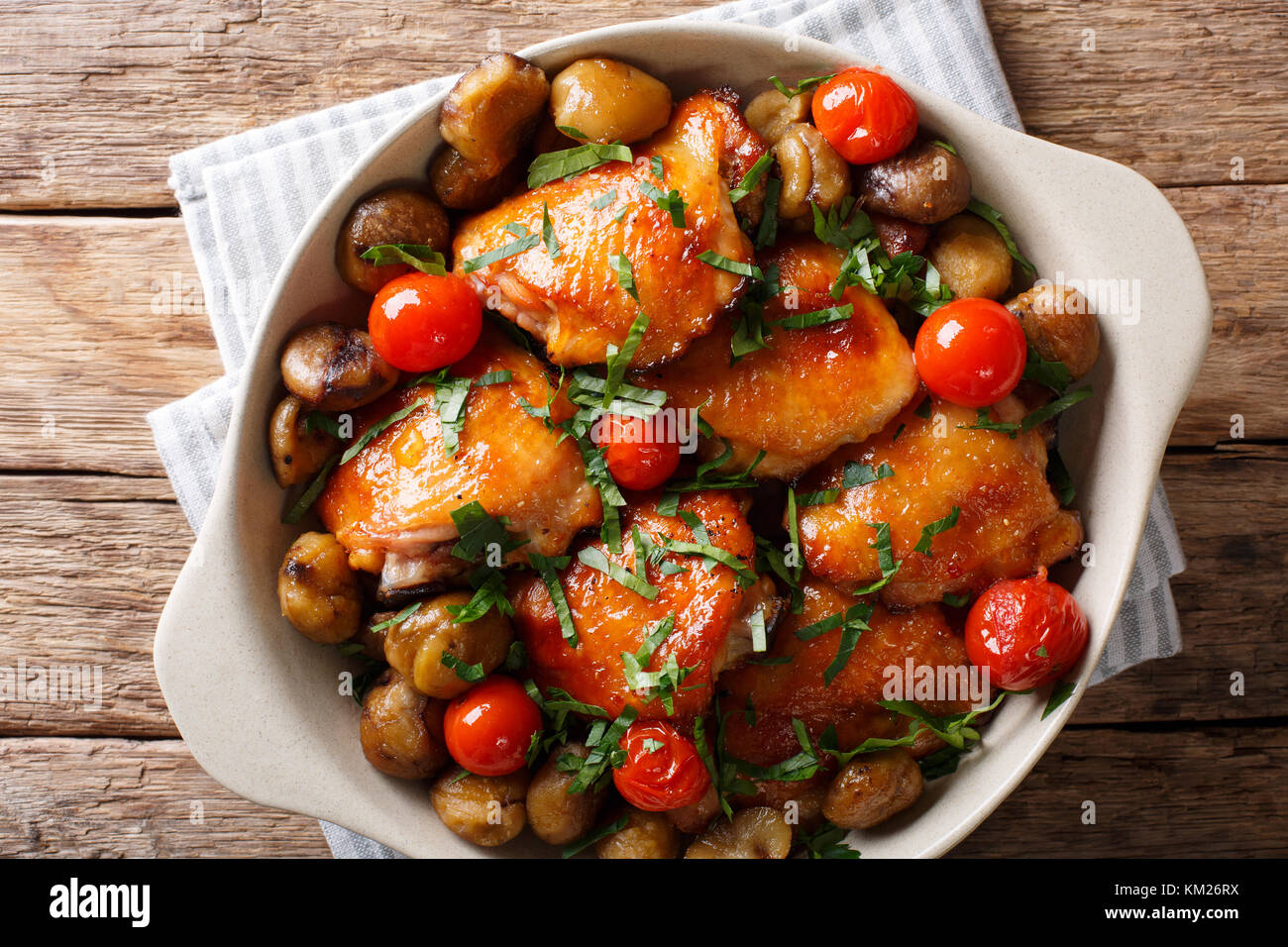 Fried chicken with chestnuts, greens and tomatoes close-up in a bowl on the table. horizontal top view from above - Stock Image
