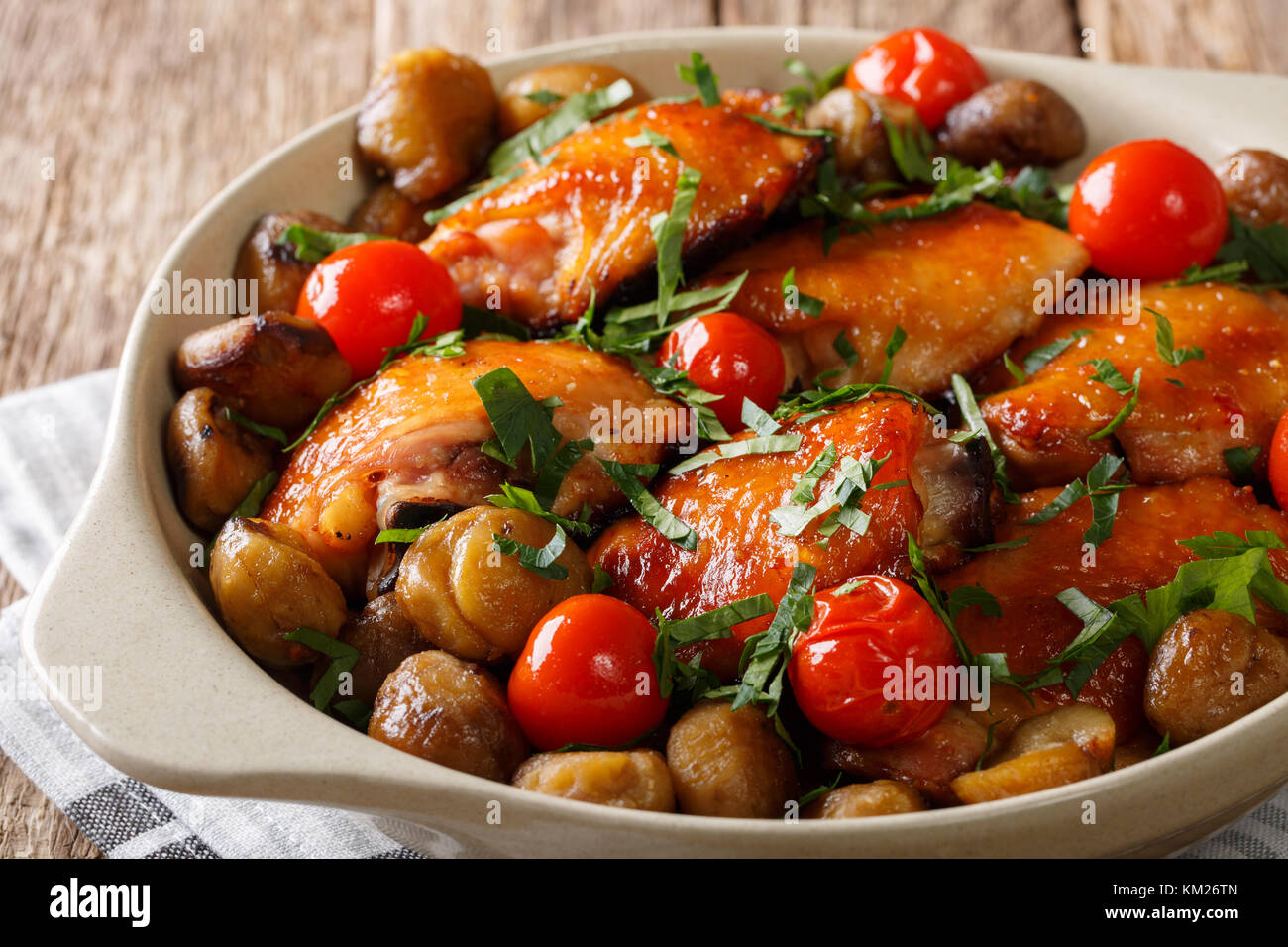 Fried chicken with chestnuts, greens and tomatoes close-up in a bowl on the table. horizontal - Stock Image