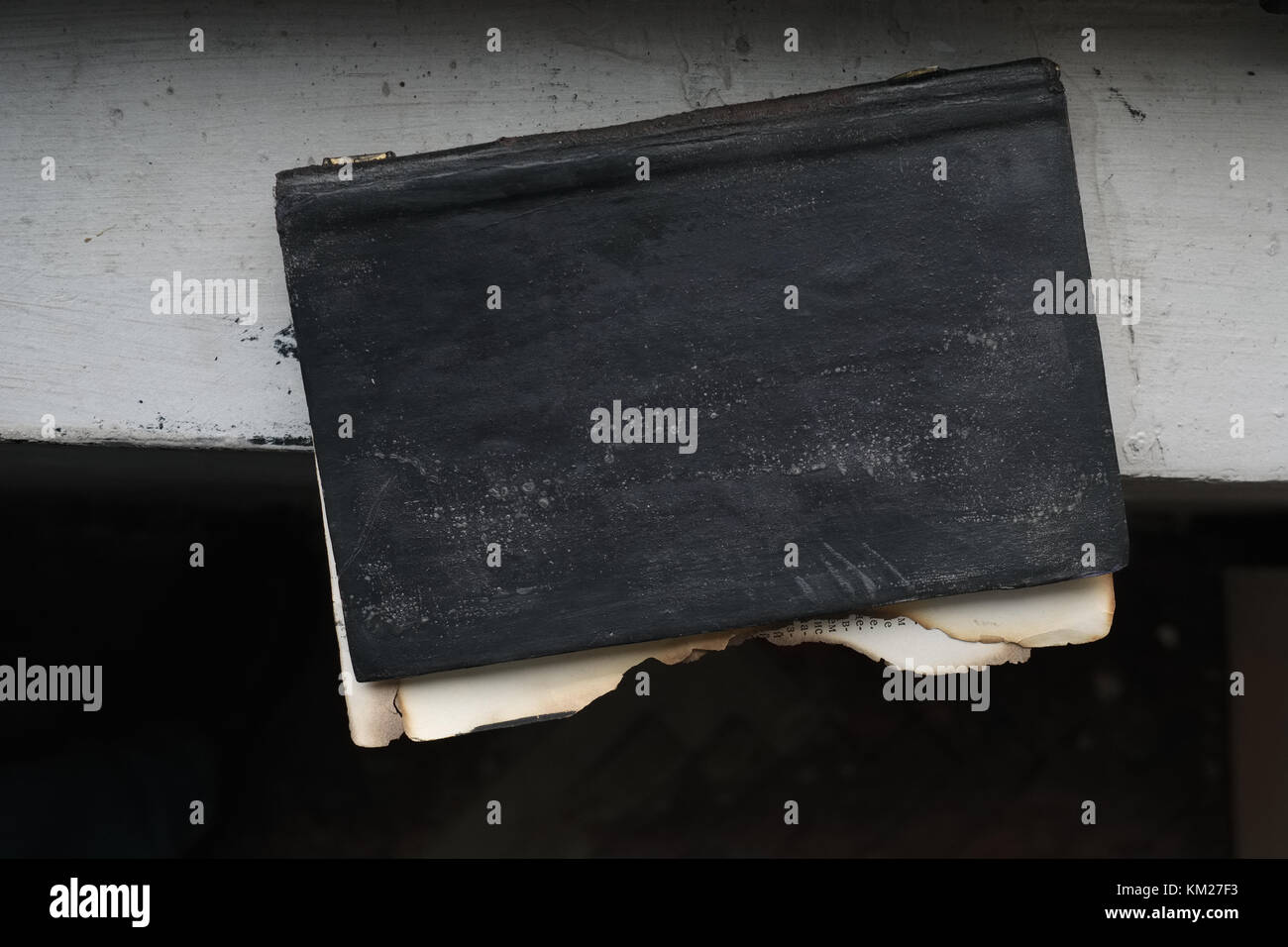 Old burnt book with teared out pages on window sill - Stock Image