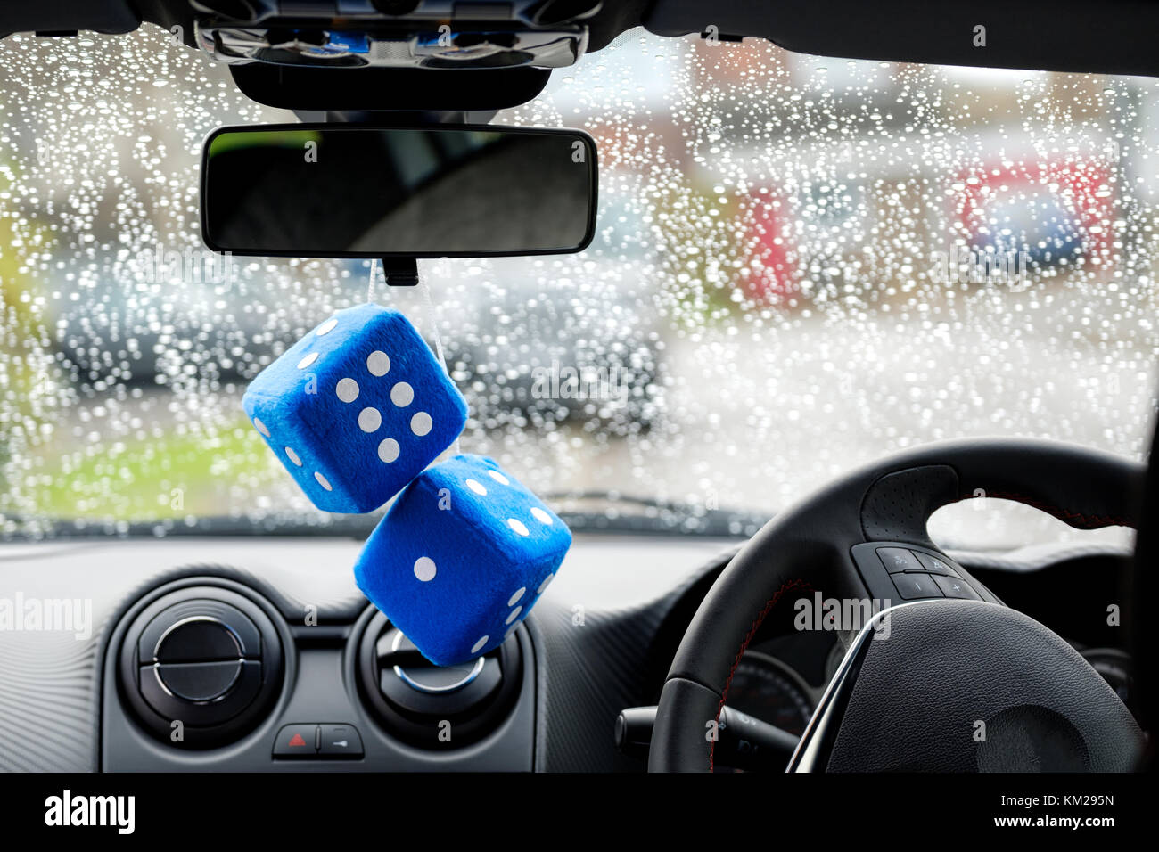 Two large, kitsch, blue, furry or fuzzy dice associated with boy racers in the seventies and eighties hang from - Stock Image