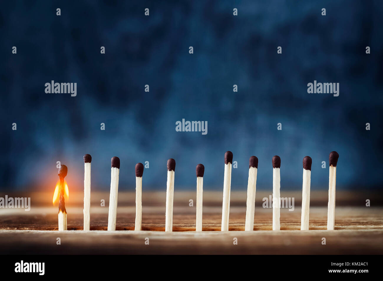 row of matches, one is lit. One burning match to the left of the rest. Concept of the idea. Top place for text - Stock Image
