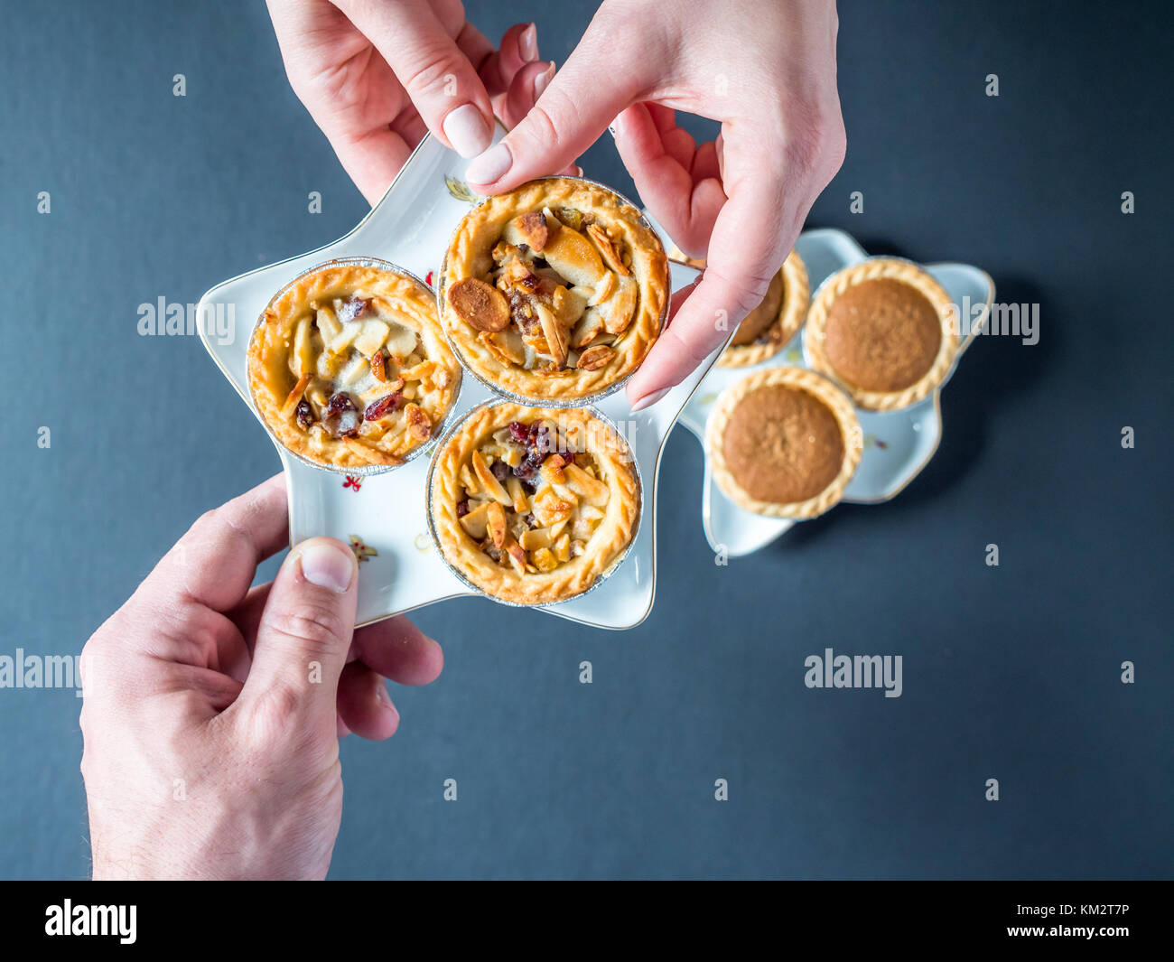 Overhead View Female Hand Grab Christmas Mince Pie Cup Cake From Festive Star Shape Plate on Dark Background. - Stock Image
