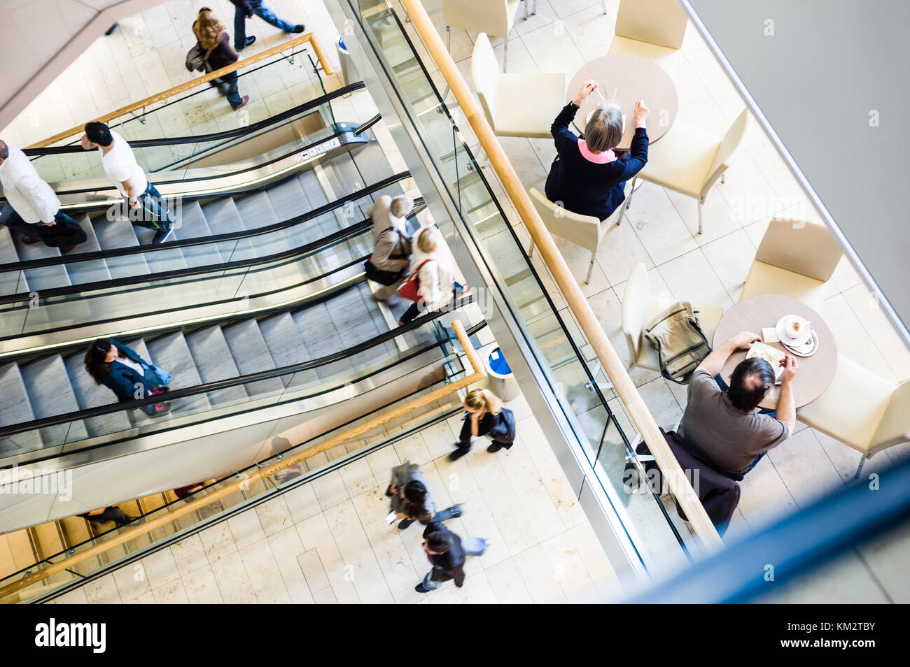 View from above of people in a shopping center taking the escalators, strolling along the walkways and having a snack on the patio of a cafe. Stock Photo