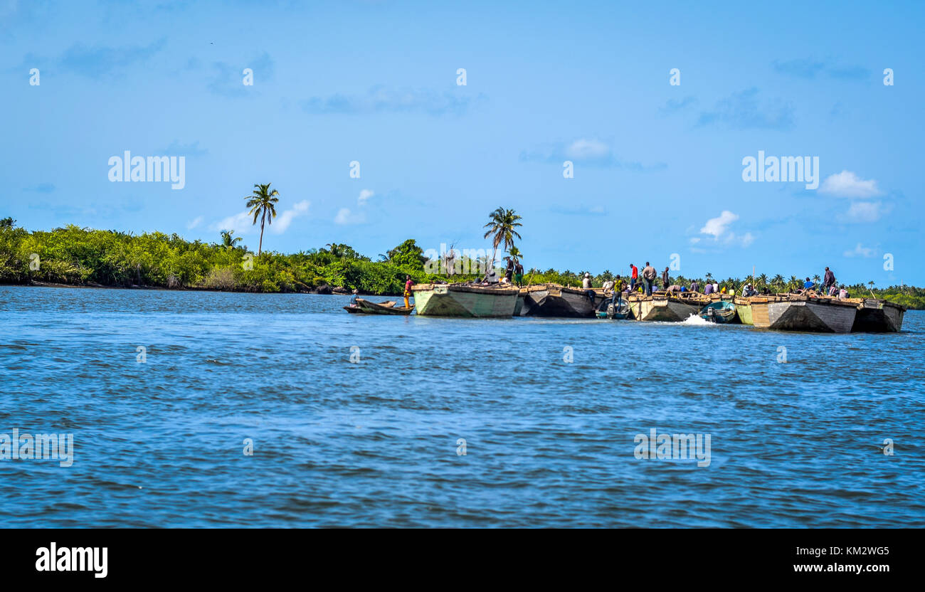 Local sand dredging  with canoes in the waters of Lagos Nigeria showing Collaboration, Bonding, Unity, Togetherness, - Stock Image