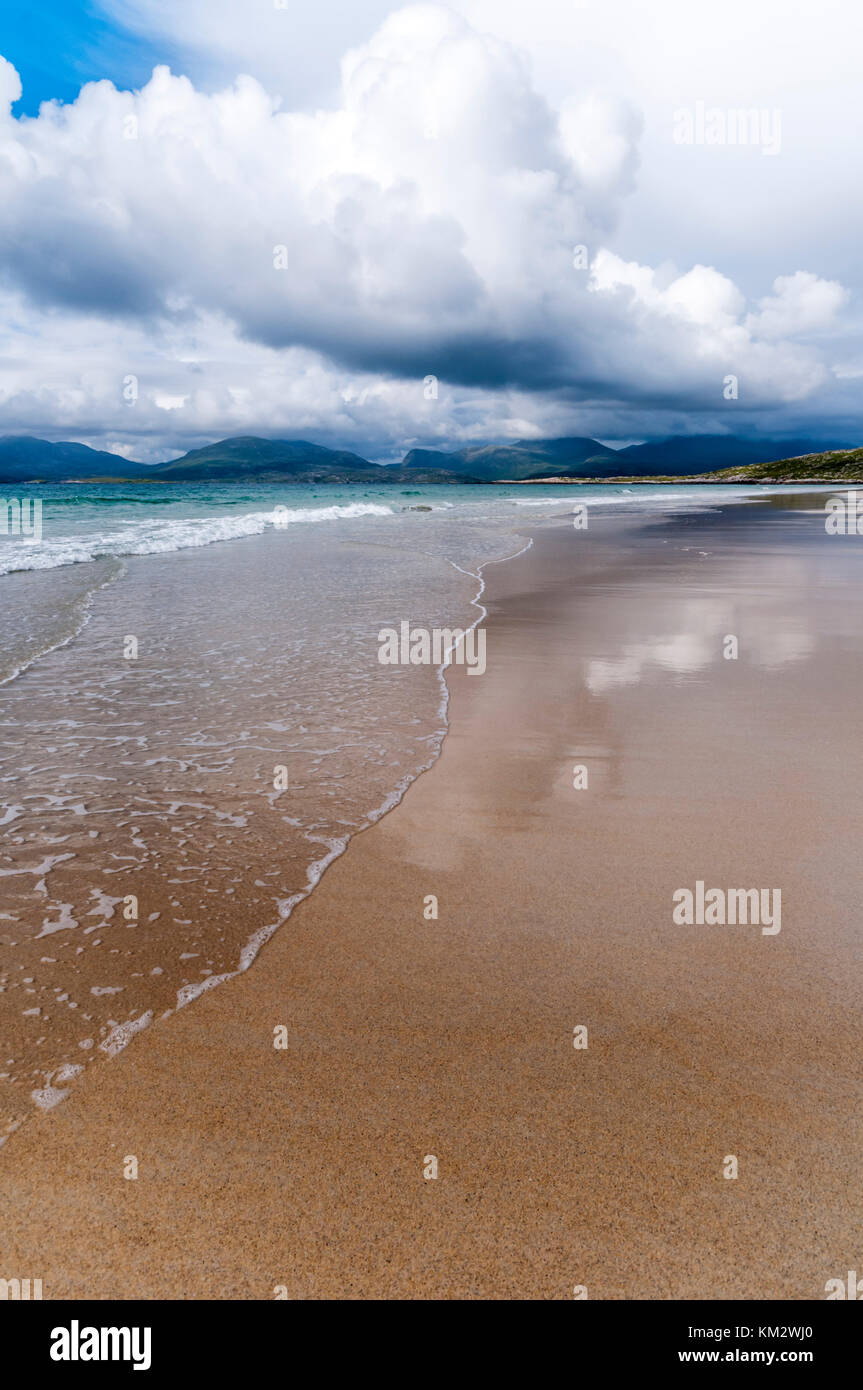Clouds reflected on the wet sand of Luskentyre beach and the Sound of Taransay on South Harris in the Outer Hebrides. - Stock Image