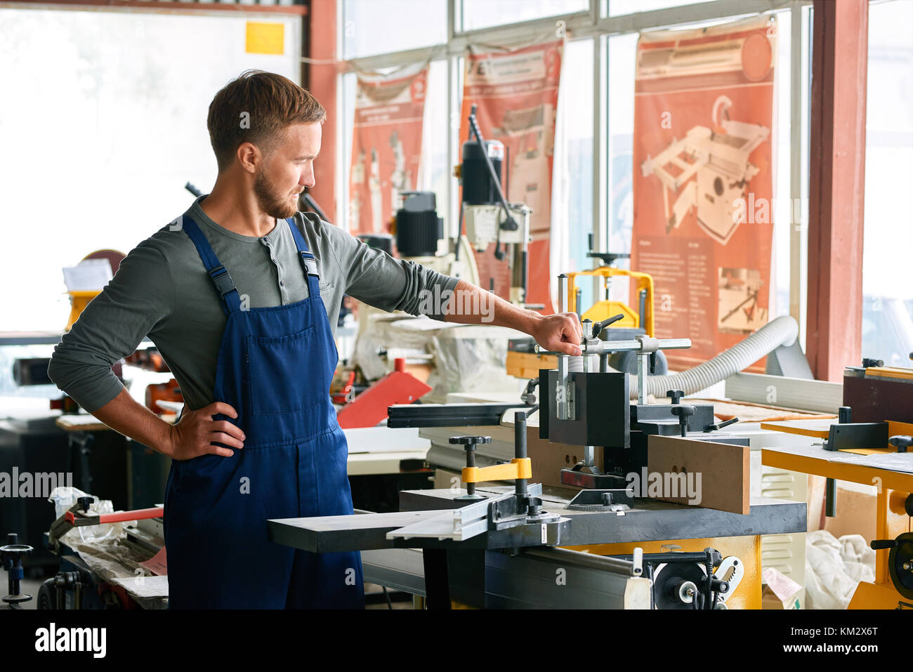 Young Workman Inspecting Machines in Shop - Stock Image
