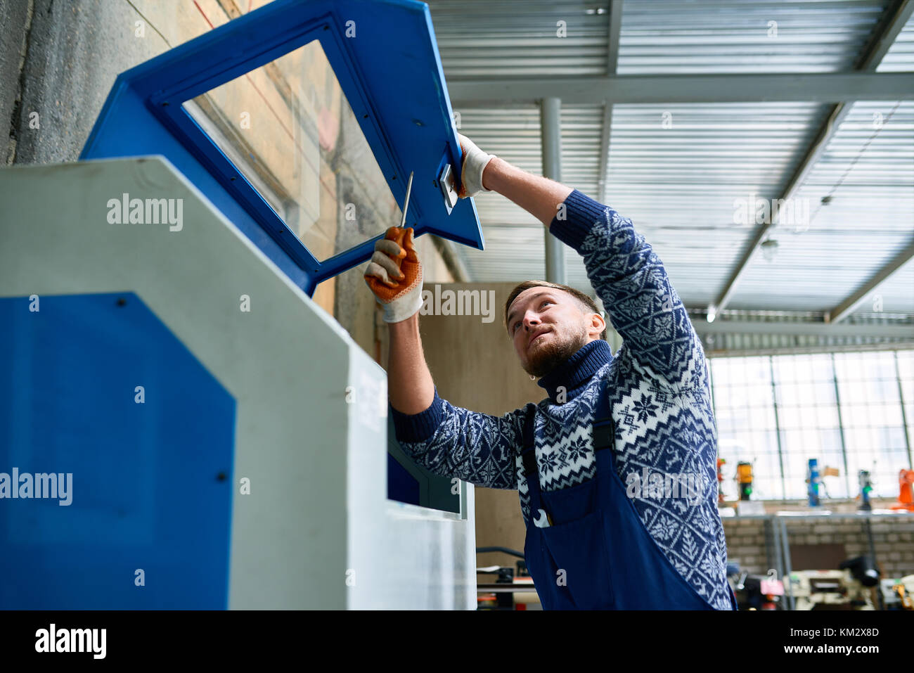 Man Fixing Machine Units at Factory - Stock Image