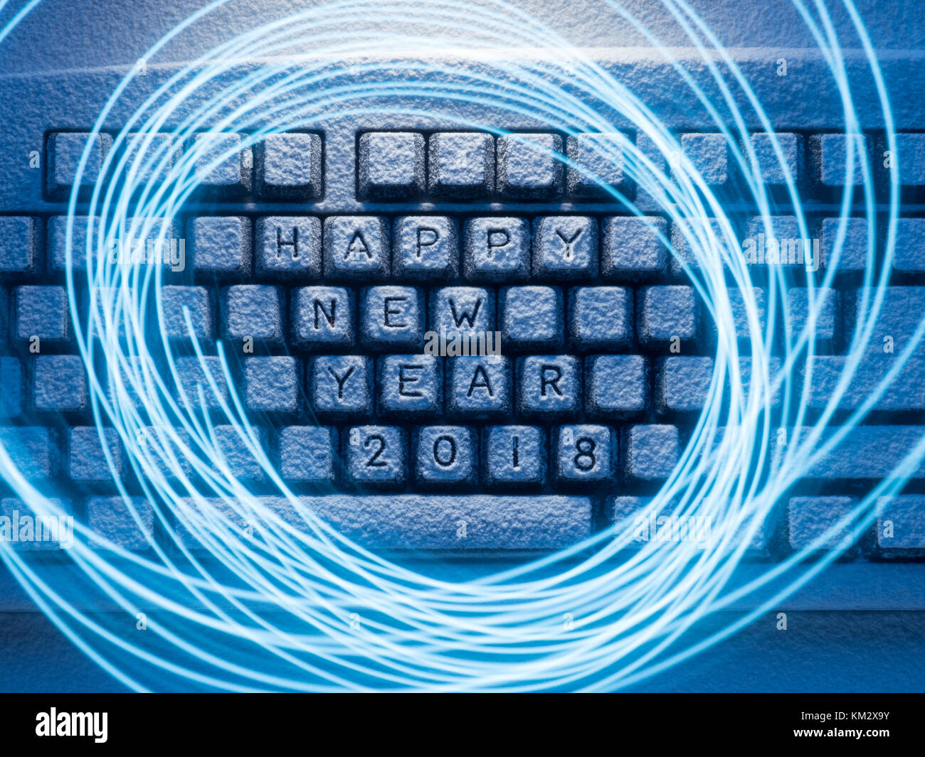 computer keyboard covered with snow illuminated by blue light with circles painted by blue light on a long exposure Stock Photo