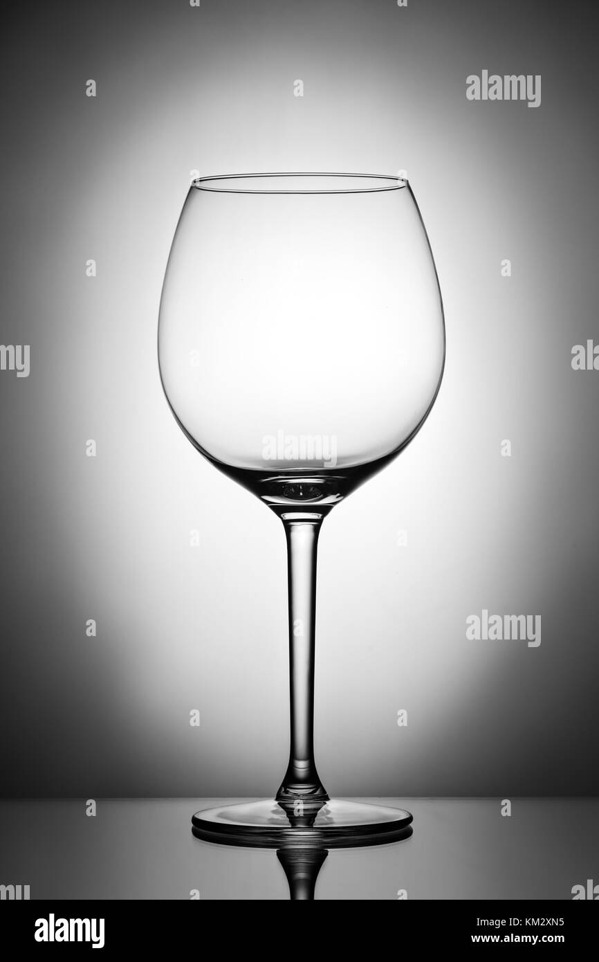 One empty wineglass for red wine on diffusion lit background, advertizing shot for restaurant, winemaking B W - Stock Image