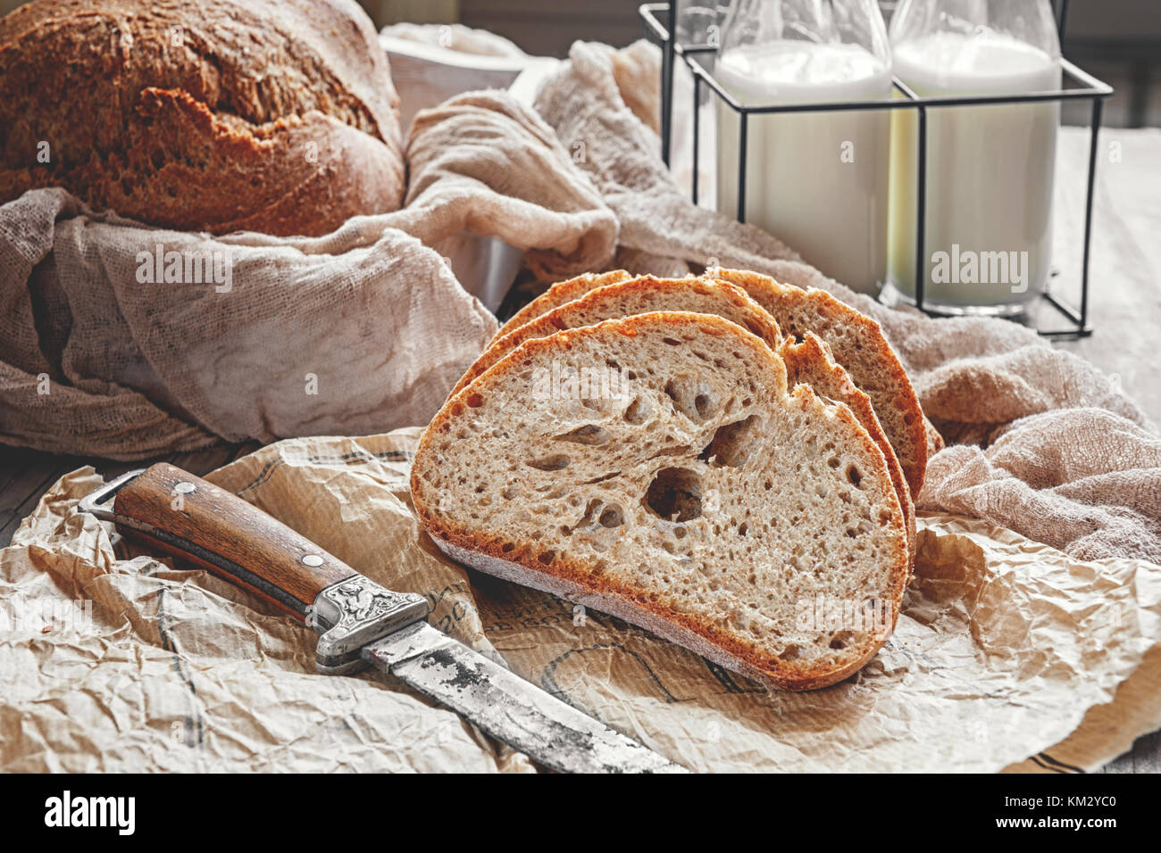 A beautiful loaf of sourdough bread from white wheat on a plate on a linen edge. Homemade pastries. - Stock Image