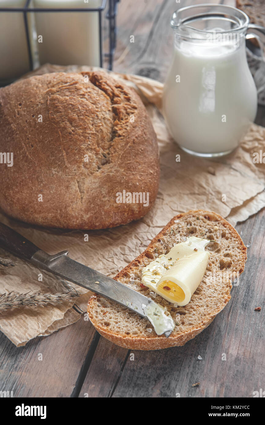 A beautiful loaf of sourdough bread from white wheat on a plate on a linen edge. Homemade pastries. In a rustic - Stock Image