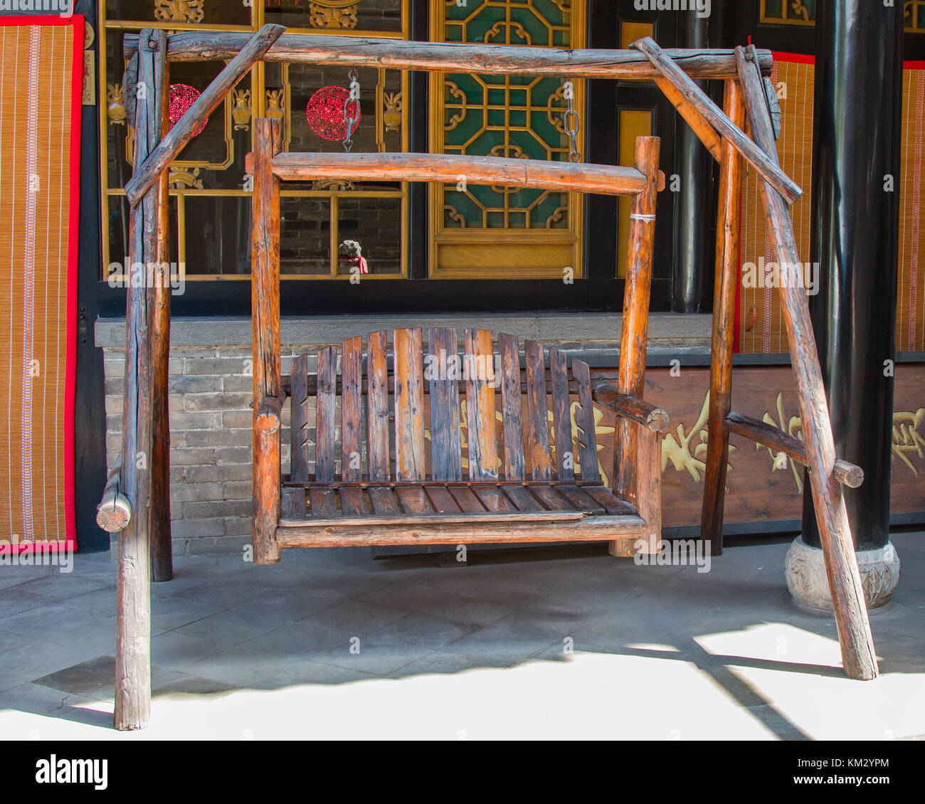 An antique twin seat swing made from chinese red pine. Stock Photo