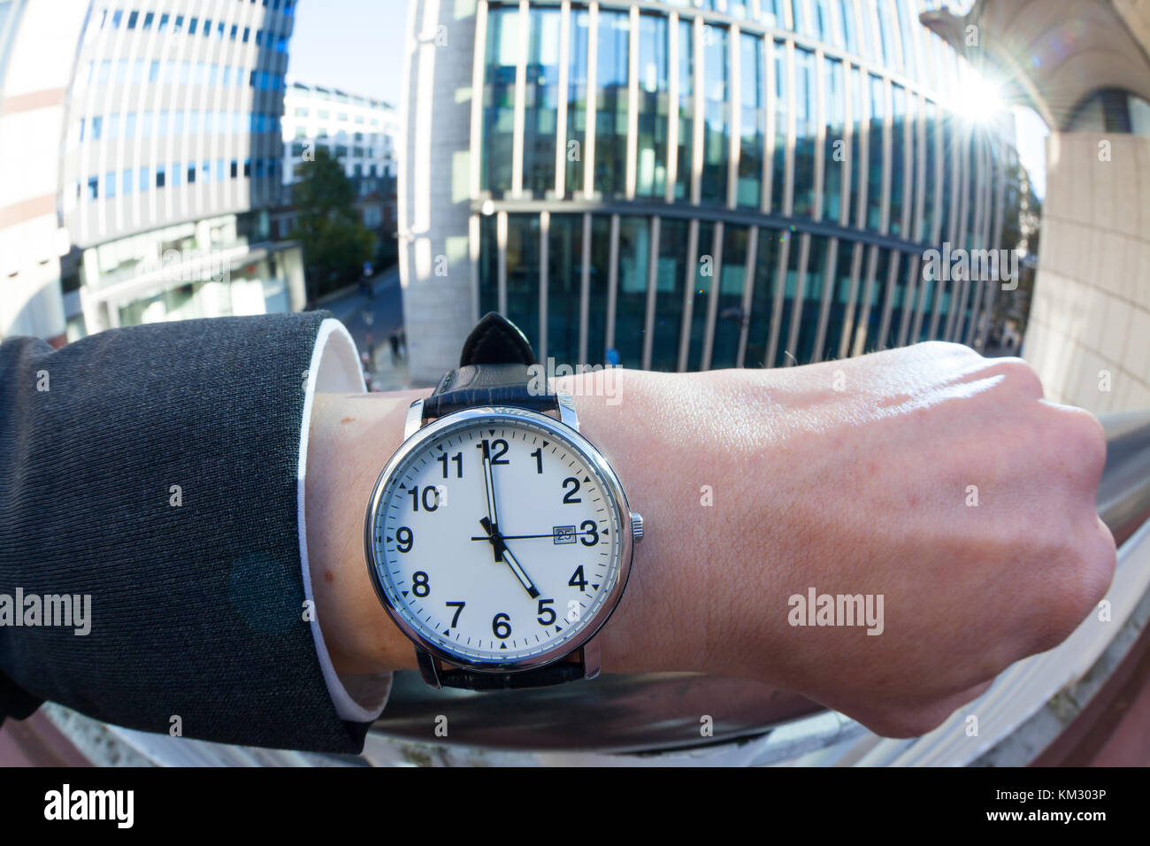 Close up of a Caucasian man wearing a wrist watch showing the time 5:00 - Stock Image