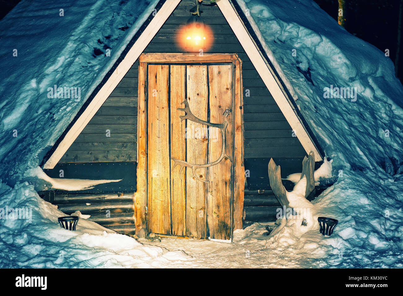 Entrance into Lappish traditional house in the reindeer farm in winter Rovaniemi, Lapland, Finland. Night snowfall. - Stock Image