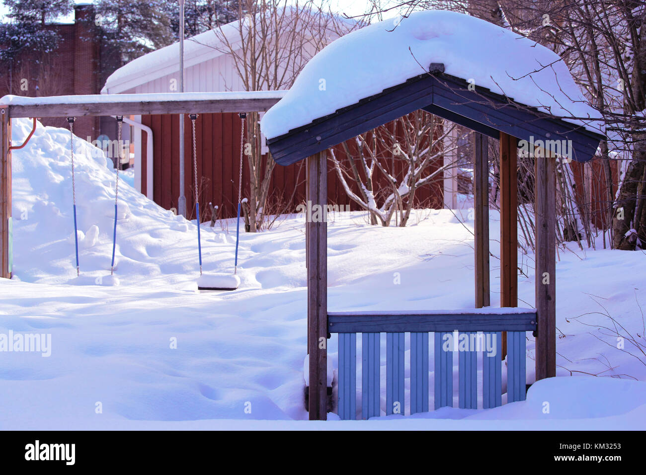 Swing covered with snow as outdoor facility in Rovaniemi, Lapland, Finland in winter - Stock Image