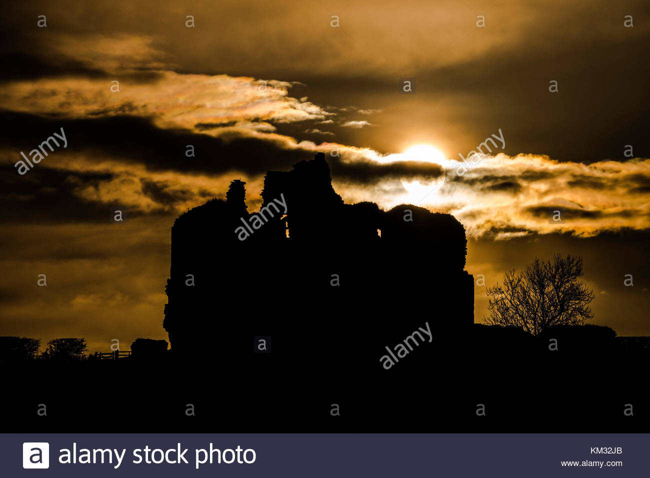 The afternoon winter sun dips behind the ruins of Cessford Castle near Kelso. in the Borders. The castle, built - Stock Image