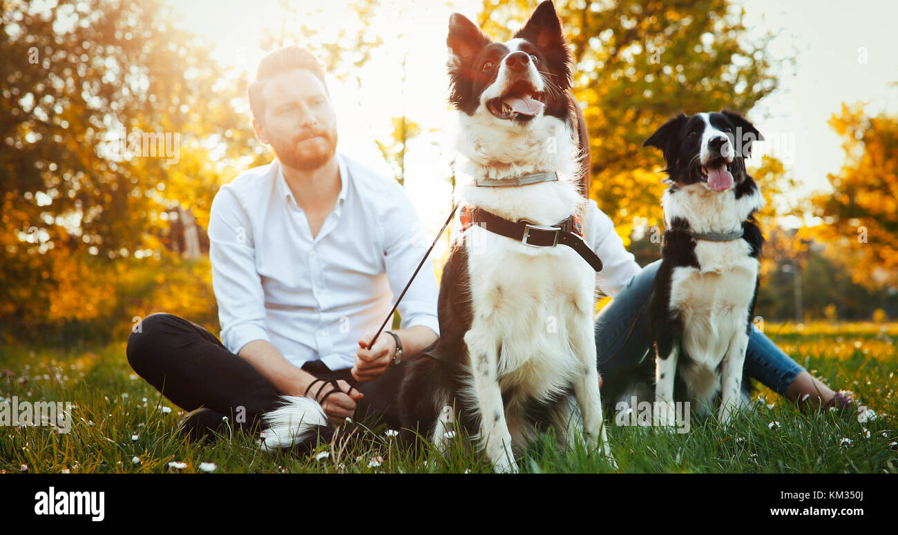 Romantic couple in love walking dogs in nature and smiling - Stock Image