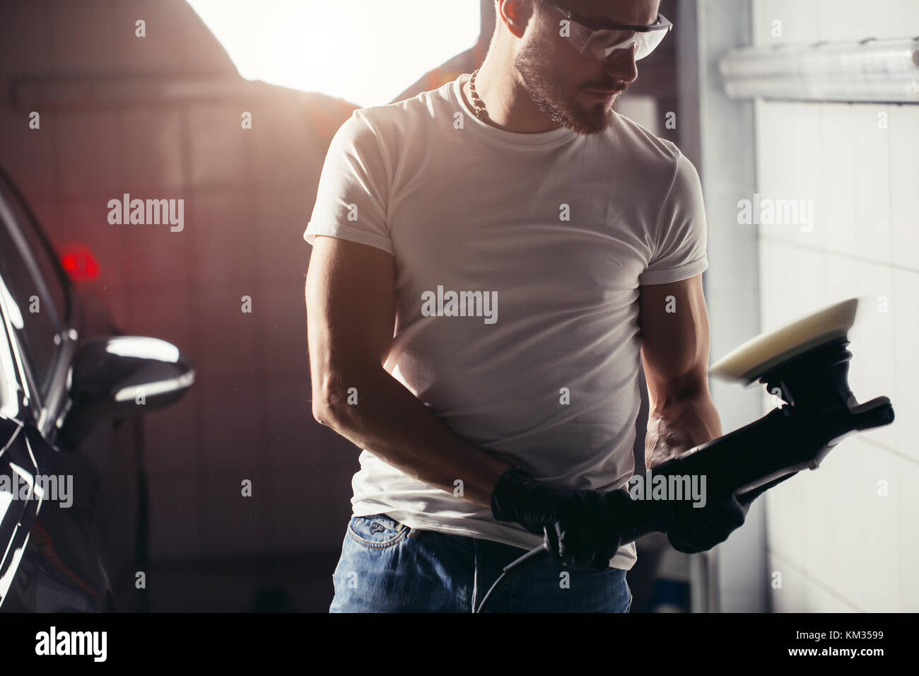 mechanic worker prepare for polishing car by power buffer machine - Stock Image