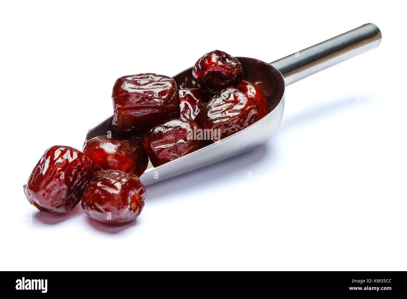Scoop full of date fruits isolated on white background. Clipping path - Stock Image