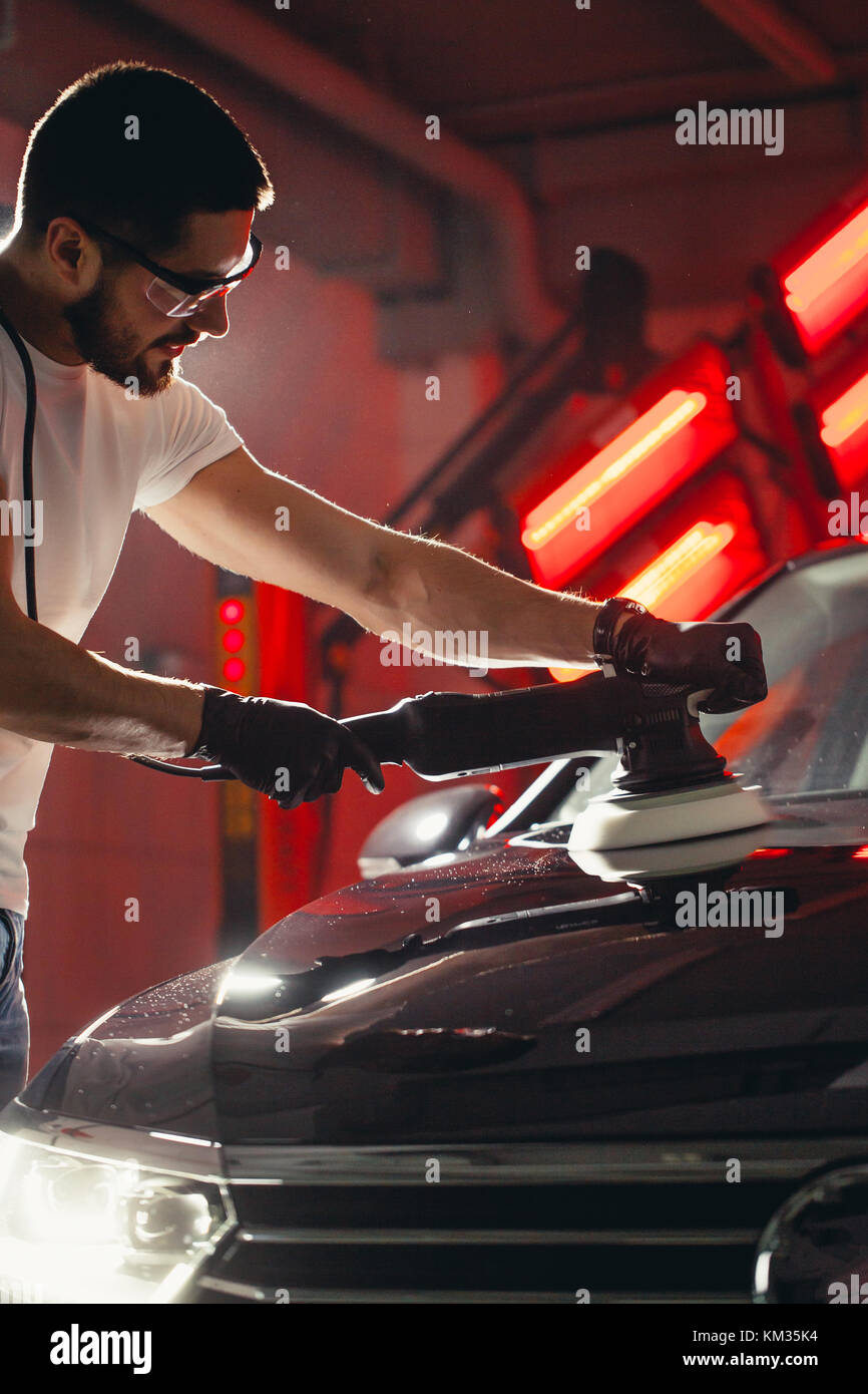 Car detailing - man with orbital polisher in auto repair shop. Selective focus. - Stock Image