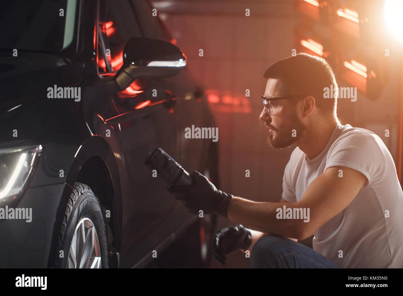 man checks polishing with a torch - Stock Image