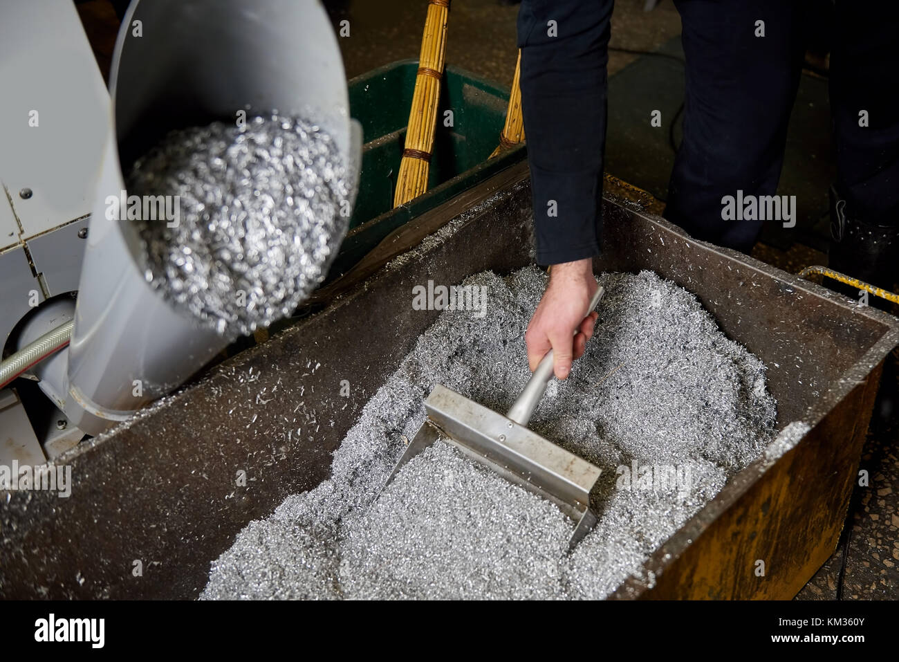 Grabing swarf from the container. Stock Photo