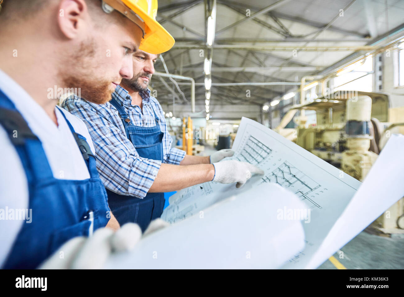 Construction Workers Inspecting Electric Scheme - Stock Image