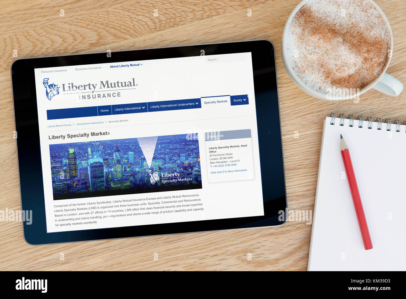 The Liberty Mutual website on an iPad tablet device which rests on a wooden table beside a notepad and pencil and - Stock Image