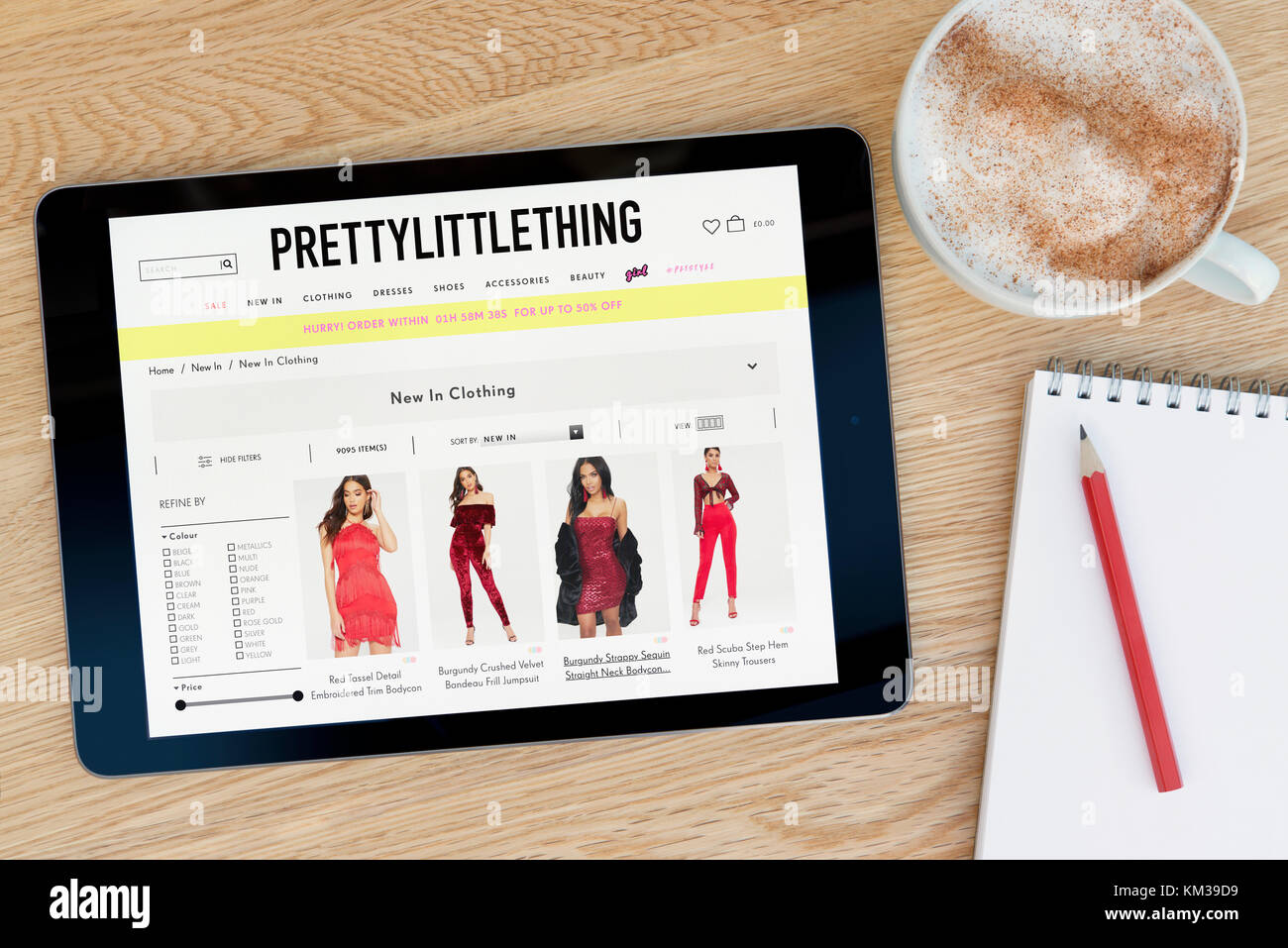 The Pretty Little Thing website on an iPad tablet device which rests on a wooden table beside a notepad & pencil - Stock Image