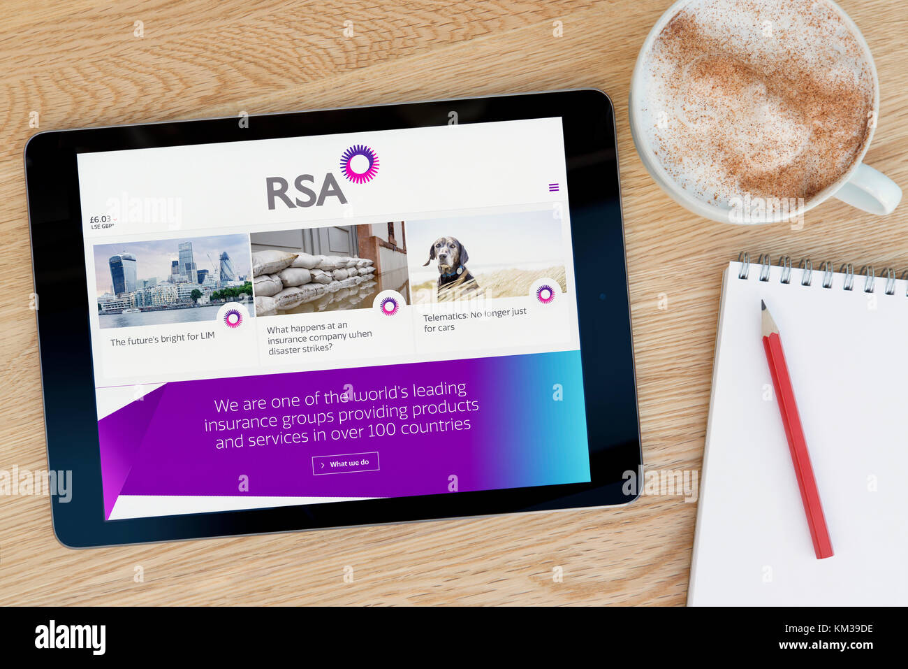 The RSA Insurance website features on an iPad tablet device which rests on a wooden table beside a notepad and pencil - Stock Image