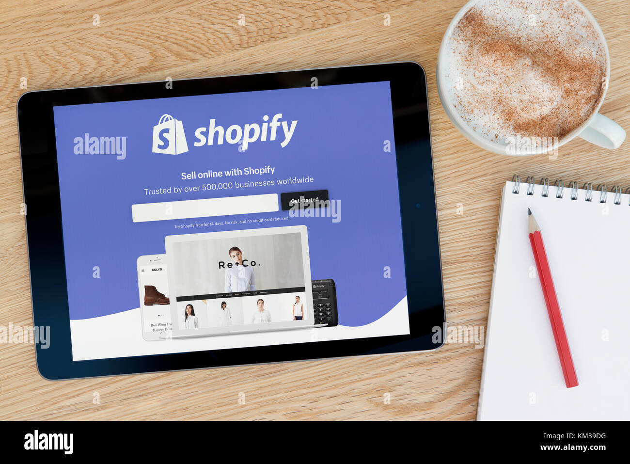 The Shopify website features on an iPad tablet device which rests on a wooden table beside a notepad and pencil - Stock Image