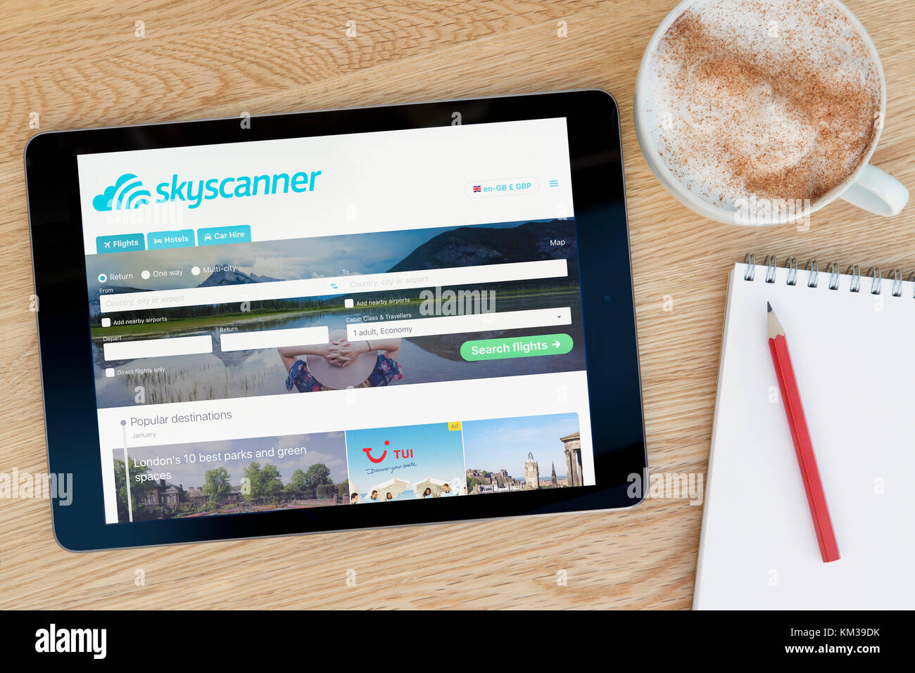 The Skyscanner website features on an iPad tablet device which rests on a wooden table beside a notepad and pencil - Stock Image