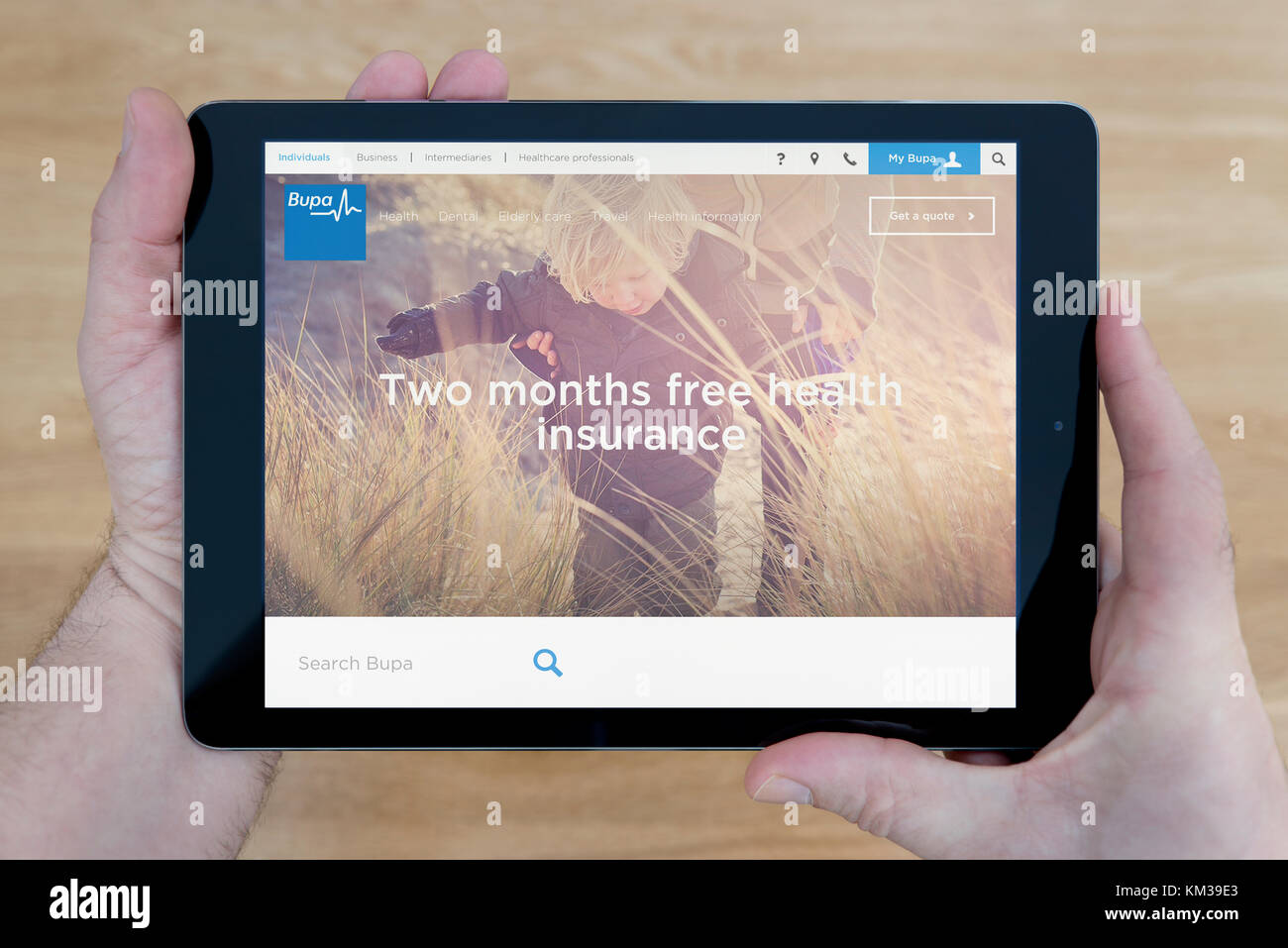 A man looks at the Bupa website on his iPad tablet device, shot against a wooden table top background (Editorial - Stock Image