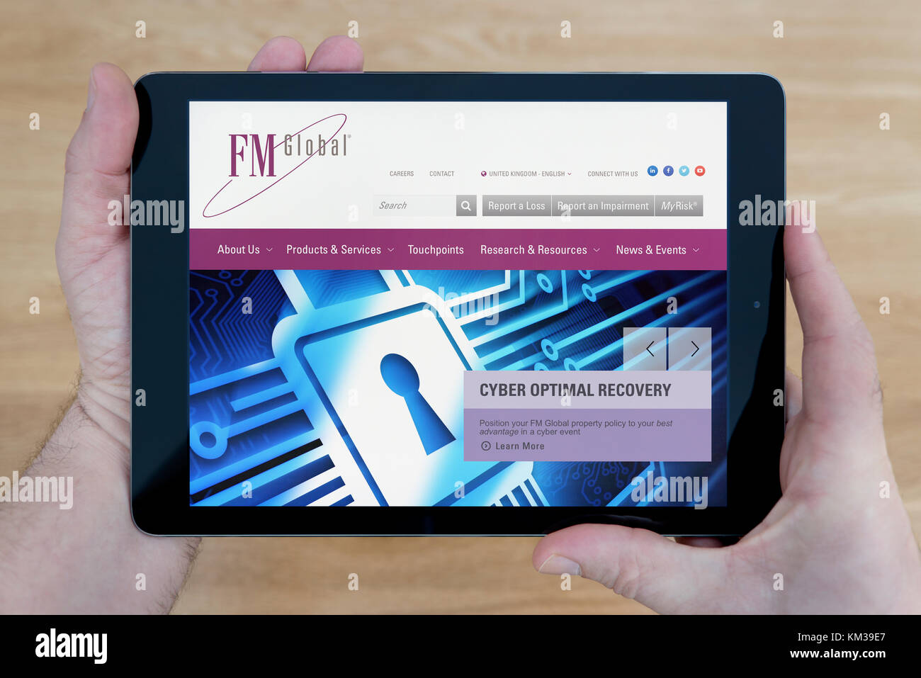 A man looks at the FM Global insurance website on his iPad tablet device, shot against a wooden table top background - Stock Image