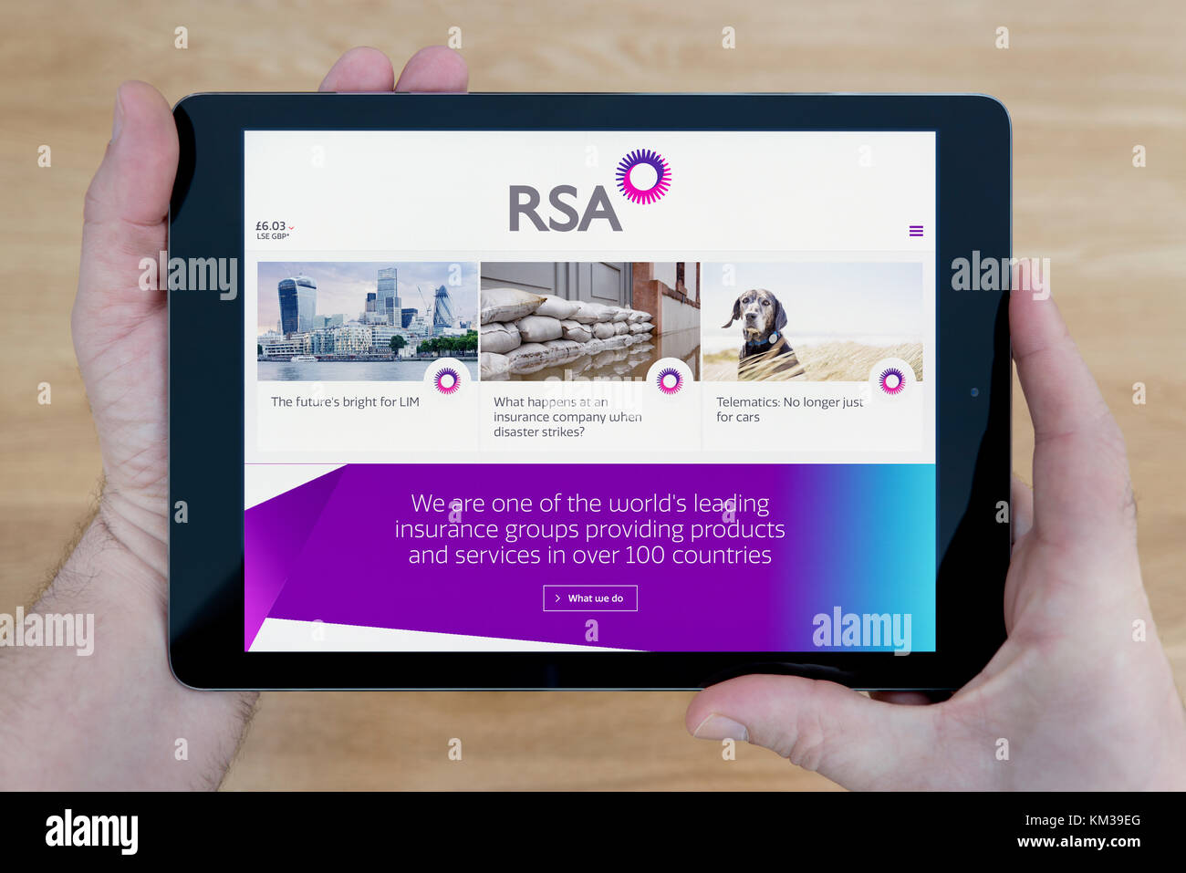 A man looks at the RSA Insurance website on his iPad tablet device, shot against a wooden table top background (Editorial - Stock Image
