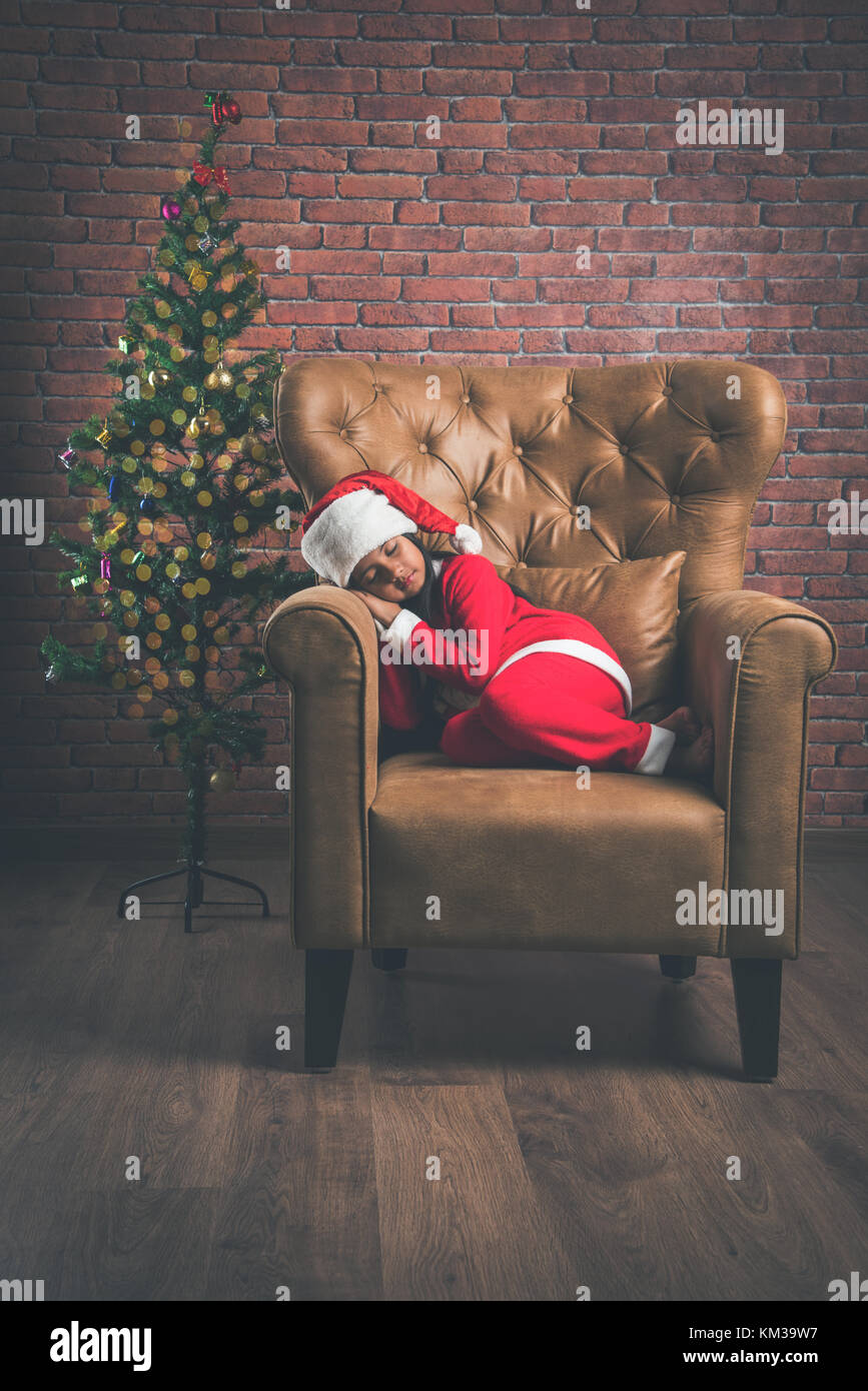 Little Indian girl with smile on face sleeping on sofa while waiting for santa clause to come with gifts. christmas - Stock Image