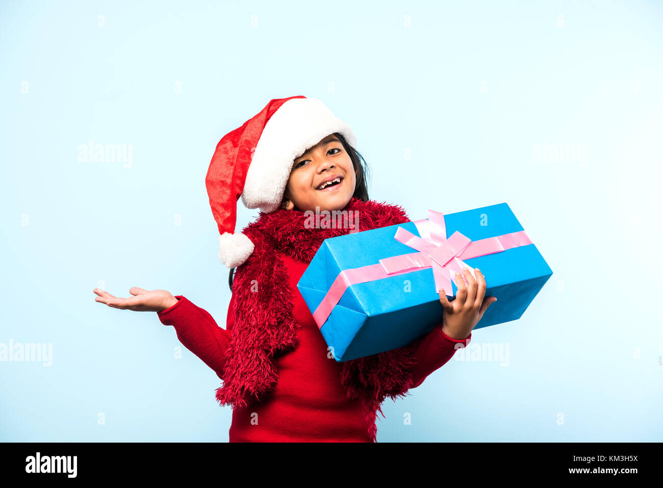 Little Indian girl holding christmas gifts in red cloths or