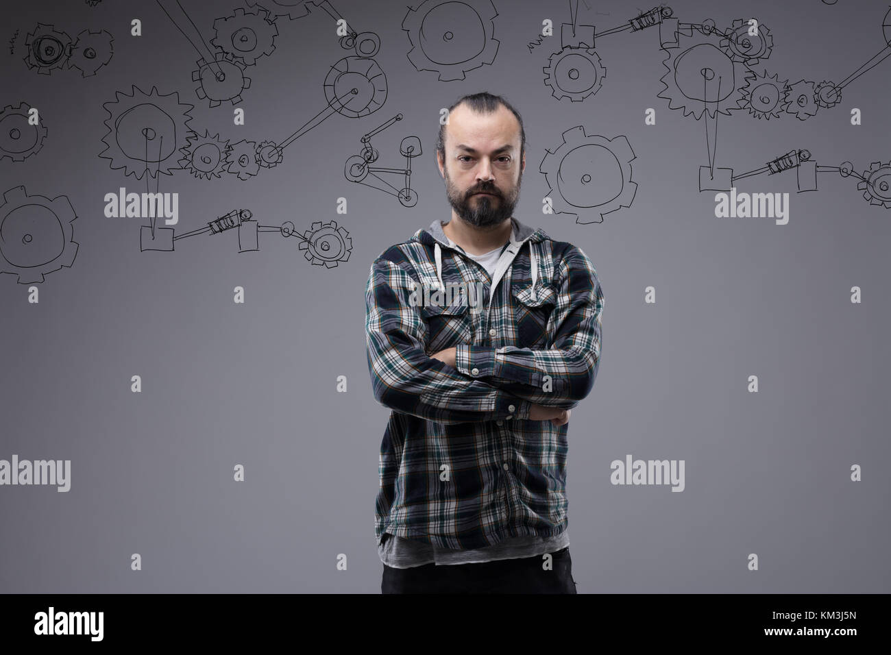 Confident bearded man with folded arms and a deadpan expression standing staring directly at the camera in an upper - Stock Image
